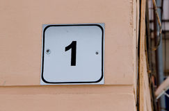 House number one. Black lettering on a white metal plate. On a wall Stock Photography