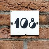 House number one hundred and eight. 108. On a brick  wall Royalty Free Stock Photo