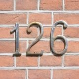 House number 126. House number one hundred and twenty six 126 Chrome lettering on a brick wall Royalty Free Stock Photos