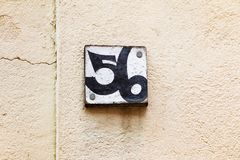House number plate fifty six 56 on old plastered wall, wooden placard. Stone background Royalty Free Stock Photography