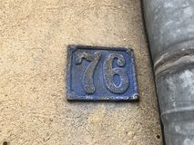 76 house number plate. Grunge number plate 76 on external wall Stock Photo