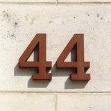 House number 44. Rusty house number forty four 44 on a stone wall Stock Photography