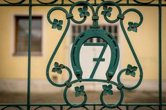 House number seven on a green iron gate. Surrounded by a horseshoe Stock Photography