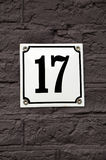 House number Seventeen. On a white iron plate that is attached to a brown, stone wall Stock Photo