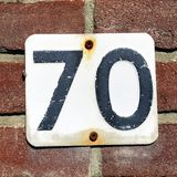 House number seventy - 70. Against a brick wall Royalty Free Stock Photography