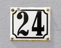 House Number 24. Sign of house number 24 in black karakters on a white sign and grey wall Stock Photography