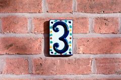 House Number 3. Sign in ceramic tile on red brick wall royalty free stock image