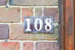 House Number 108 sign. Fixed to red brick wall Stock Photos