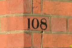 House number 108 sign painted on wall. House number 108 sign painted black on wall Royalty Free Stock Photography