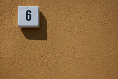 House number, six, outside textured wall, copy space Royalty Free Stock Image