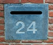 House number 24 in stone. A postbox from granite with the house number twentyfour on it between red bricks Royalty Free Stock Photos