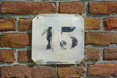 House number thirteen 13. On a brick wall Royalty Free Stock Photos
