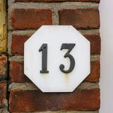 House number thirteen 13. On a brick wall Stock Photo