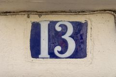 House number thirteen 13. Embedded in a plastered wall Royalty Free Stock Photos
