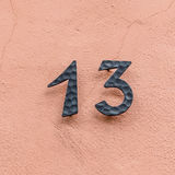 House number thirteen at a pink wall Stock Image