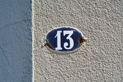 House number thirteen 13. On a plastered wall Royalty Free Stock Images