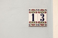 House number thirteen, sign at wall Royalty Free Stock Photography