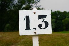 House number thirteen 13. Template lettering on a plate near some gras Stock Photography