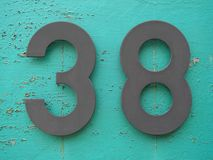 House number thirty eight. Black number thirty eight on blue background stock image