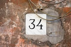 House number 34 engraved in stone. House number thirty four 34 engraved in stone on an old wall Royalty Free Stock Image