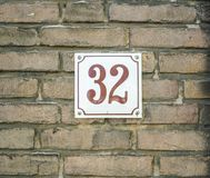 House Number 32 thirty two. brown numbers on a white plate const Royalty Free Stock Photos
