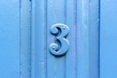 Number 3. House number three 3 on a blue painted door Royalty Free Stock Photo