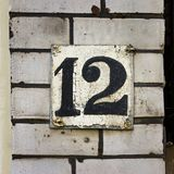 House number twelve 12. On a brick wall Stock Image