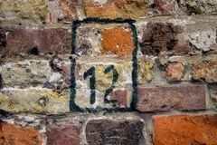 House number twelve 12. On a brick wall Stock Photography