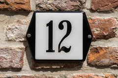 House number twelve 12. On a brick wall Stock Images