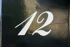 House number twelve 12. Painted on a lacquered door Stock Photography