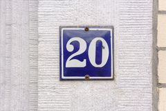 Enameled house number 20. House number twenty 20. Enameled sign on a stone wall Stock Photography