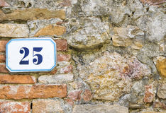 A house number twentyfive (25) on a wall in Pienza, Tuscany Stock Photography