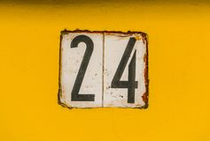 House number 24. White metal black numbers on yellow South American wall Stock Image