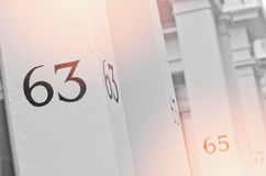 House number 63 on white pillar in London. Royalty Free Stock Photos