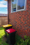 House. Old style  brick house with garbage bins Royalty Free Stock Images