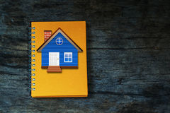 House  on  orange  notebook  on  vintage  wood  background. Royalty Free Stock Photos