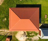 House with an orange roof made of metal, top view. Metallic profile painted corrugated on the roof. House with an orange roof made of metal, top view. Metallic royalty free stock photography