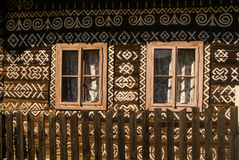 House with ornaments. Old wooden house with two windows and many white ornaments painted on its wall in Cicmany, old village in Slovakia Royalty Free Stock Photo
