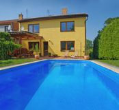 House with outdoor swimming pool. Yellow house with outdoor swimming pool on the garden Royalty Free Stock Photos