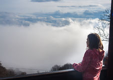 House over the clouds. A girl looking over the clouds stock photos