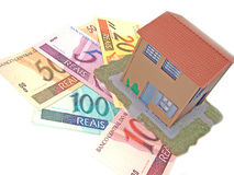 House over money. Little model house over a lot of brazilian real banknote stock images