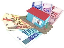 House over money. Little model house over a lot of brazilian real banknote royalty free stock photography