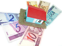 House over money. Little model house over a lot of brazilian real banknote royalty free stock images