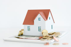 House ownership concept – a model house on a pile of coins. House ownership concept – a model house with coins and dollar bills around Stock Photography