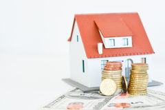 House ownership concept – a model house on a pile of coins. House ownership concept – a model house with coins and dollar bills around Stock Photo