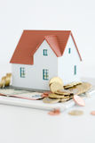 House ownership concept – a model house on a pile of coins. House ownership concept – a model house with coins and dollar bills around Royalty Free Stock Images