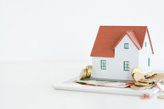 House ownership concept – a model house on a pile of coins. House ownership concept – a model house with coins and dollar bills around Stock Image