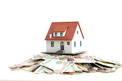 House ownership concept – a model house on a pile of dollar bills Royalty Free Stock Image