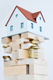 House ownership concept – a model house on a pile of coins Royalty Free Stock Photography