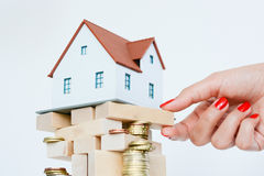 House ownership concept – a model house on a pile of coins Stock Photo